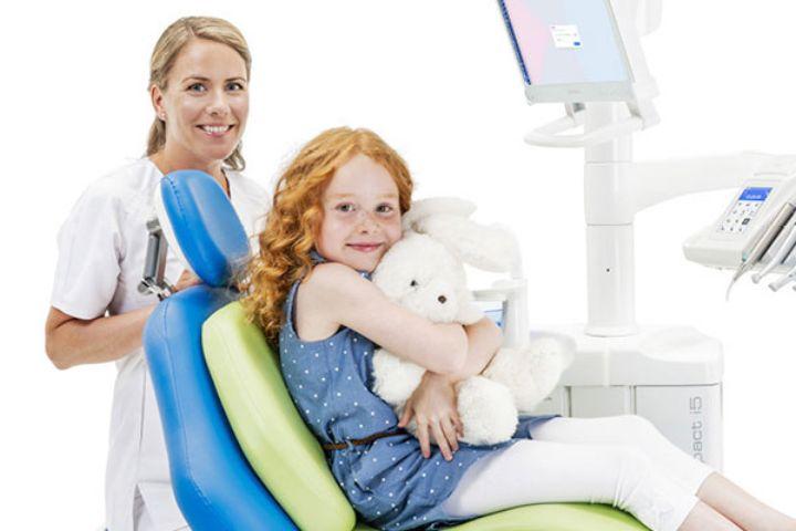 En lille pige med en bamse i favnen sidder på en tandlægeunit med ergonomiske puder for korrekt sidestilling